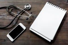 Concierte una cita con el doctor por mofa de escritorio de madera oscura del cuaderno de la opinión del teléfono celular para arr Imagenes de archivo