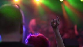 Concierto de rock fresco de la noche en la primera fila de la muchedumbre de aplauso bajo luz de la iluminación Primer de la cáma metrajes