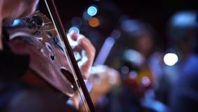 Concierto, una mano del músico que toca el violín, cierre encima del tiro almacen de metraje de vídeo