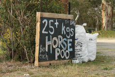 Concime del cavallo da vendere vicino ad una proprietà del paese Fotografie Stock
