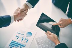 Concluding contract. Managers shaking hands over business plans Royalty Free Stock Photography