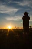 Conclusione di un Safari giorno, tramonto di sorveglianza dell'uomo in savana africana Immagini Stock