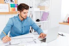Concntrated ung affärsman med dokument och bärbar dator på kontoret royaltyfri bild