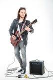 Concntrated ung manlig gitarrist som spelar den elektriska gitarren och använder förstärkaren Fotografering för Bildbyråer