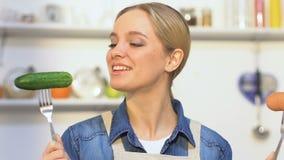 Concombre acéré de fille gaie, choisissant entre le légume et la saucisse, vitamines clips vidéos