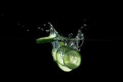 Concombre coupé en tranches éclaboussant l'eau Photographie stock libre de droits