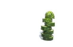Concombre coupé en tranches d'isolement sur la verticale blanche Images stock