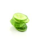 Concombre coupé en tranches dans la pile d'isolement sur le fond blanc Photo stock