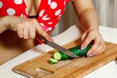 Concombre coupé en tranches par femme sur une planche à découper Image stock