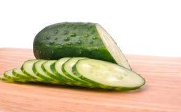 Concombre coupé en tranches sur le panneau de découpage Image libre de droits