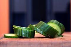 Concombre coupé en tranches sur une planche à découper en bois Images stock