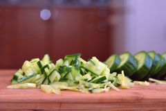 Concombre coupé en tranches sur une planche à découper en bois Photos libres de droits