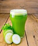 Concombre de jus en verre à bord Images stock
