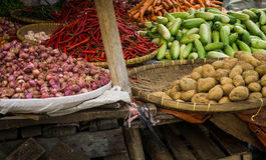 Concombre de pomme de terre d'oignon rouge et piments rouges avec le panier en bois en bambou sur le marché traditionnel de Bogor Image libre de droits