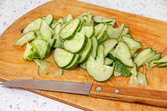 Concombre et couteau coupés en tranches frais sur la planche à découper en bois Photo stock