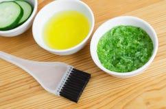 Concombre et huile d'olive râpés dans petites cuvettes en céramique pour préparer le masque facial naturel Cosmétiques faits mais Images stock