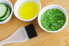 Concombre et huile d'olive râpés dans petites cuvettes en céramique pour préparer le masque facial naturel Cosmétiques faits mais Photo stock