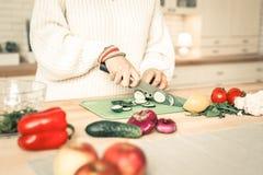 Concombre qualifié précis de coupe de femme avec le couteau professionnel photos libres de droits