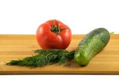 Concombre, tomate et aneth sur le conseil en bois images libres de droits