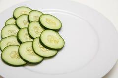 Concombres coupés en tranches d'un plat blanc Photos libres de droits