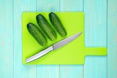 Concombres et couteau sur une planche à découper image stock