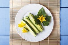 Concombres et feuilles de Sliceb avec les fleurs jaunes du plat blanc Vue supérieure sur la table en bois avec le tapis en bambou photographie stock