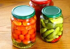 Concombres et tomates en boîte Images stock