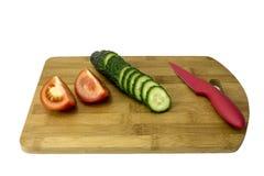 Concombres et tomates sur une planche à découper Image stock