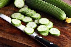Concombres frais et coupés en tranches Concombres coupés en tranches sur une planche à découper Photographie stock libre de droits