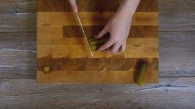 Concombres marinés coupés en tranches par mains de femmes banque de vidéos