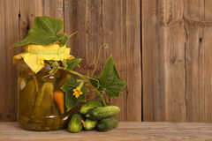Concombres salés faits maison en concombres frais de pot en verre Pot de concombres en boîte sur le fond en bois Images stock