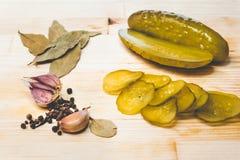 Concombres verts marinés, ail frais et épices sur un conseil en bois photos libres de droits