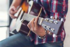 Concorde a corda, fim acima das mãos dos homens que jogam uma guitarra acústica Fotografia de Stock Royalty Free