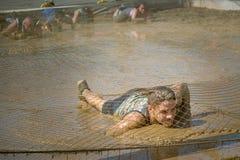 Concorrente che striscia attraverso il fango nella corsa ad ostacoli immagini stock