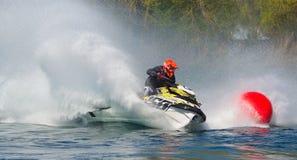 Concorrente de Jet Ski que encurrala na velocidade que cria no lote do pulverizador Fotos de Stock