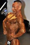 Concorrente masculino do halterofilismo que mostra sua pose da caixa Foto de Stock Royalty Free