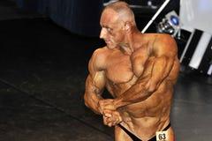 Concorrente masculino do halterofilismo que mostra sua pose da caixa Fotos de Stock Royalty Free