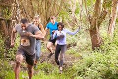 Concorrenti che corrono in una foresta ad un evento di resistenza Fotografie Stock