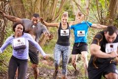 Concorrenti che corrono in una foresta ad un evento di resistenza Immagine Stock