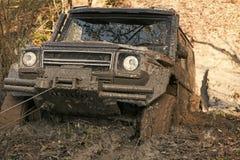 Concorrenza delle automobili fuori strada SUV è estratto dalla pozza di fango dall'argano dell'automobile Fotografie Stock Libere da Diritti