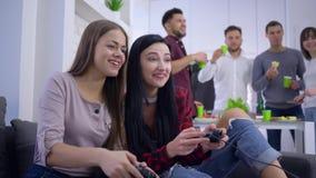 Concorrenza di conquista del videogioco dell'adolescente femminile con l'amica che si siede sul sofà su backgrounf della società  stock footage