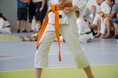 Concorrenza di karatè una ragazza in kimono con la cinghia arancio Nessun fronte fotografie stock