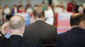 Concours d'art martial - trois entraîneurs chauves d'hommes regardant le karaté badinent le combat du ` s banque de vidéos