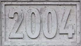 Concreet blok met het jaar gegraveerde 2004 Stock Afbeelding