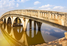 Concrete arch bridge cross the canal. In public the park on sunset Stock Photography