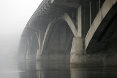Concrete arch bridge over the river in the fog.  Stock Photography