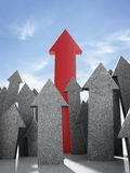 Concrete arrows with red one against the sky Stock Image