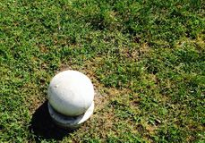 Round concrete ball on green grass Stock Image