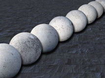 Concrete balls 1. Row of concrete balls on slate tiles Royalty Free Stock Images