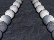 Concrete balls 1. Two rows of concrete balls on slate tiles Stock Photography